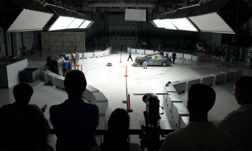 People on the observation deck watch as engineers inspect a car after a crash test at the Vehicle Research Center (VRC). The VRC was the site of today's announcement regarding automatic emergency braking.