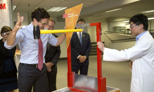 Prime Minister Justin Trudeau at 3M's Canadian headquarters, swinging a hammer at a new super-strong tape being developed as an alternative to rivets and fasteners.