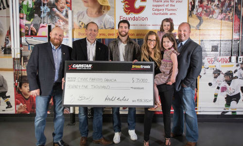 Presenting the donation to Cystic Fibrosis Canada. From left: Scott Lavery of CARSTAR, Michael Piper of CARSTAR, T.J. Brodie of the Calgary Flames, Candace Goldie of the Calgary Flames Foundation and Brand Newell of Cystic Fibrosis Canada and his family.
