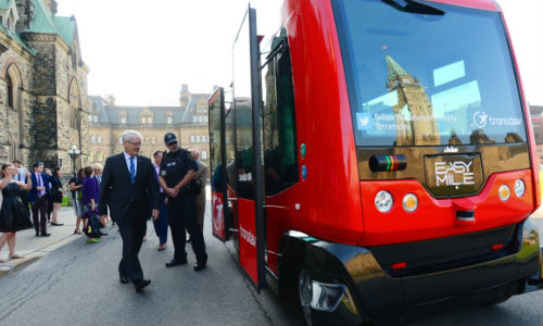 Transport Minister Marc Garneau prepares to board an automated bus built by TransDev during a demonstration on Parliament Hill on Wednesday.