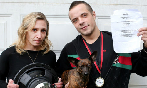 Dustin Hamilton with his girlfriend, Katrina Jourdenais, and their dog, Luna. Hamilton is a professional car audio installer, but it turns out his neighbours think he's too good at his job. The sheet of paper he's holding was put up in his neighbourhood, asking residents to complain to police about his car stereo.