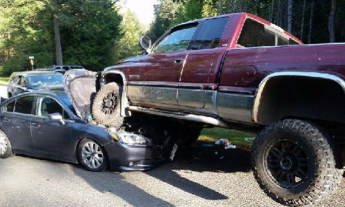 Two Vancouver Island men are in custody after two police vehicles were destroyed by a Dodge pickup that drove over the cars as the officers approached.